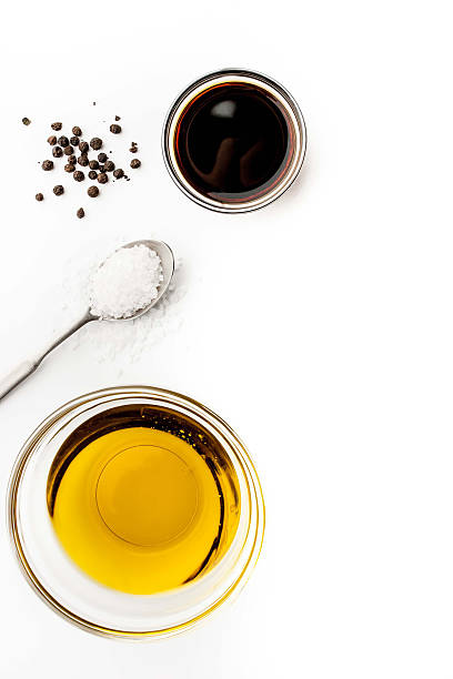olive oil with seasoning on the white background vertical - balsamico stockfoto's en -beelden