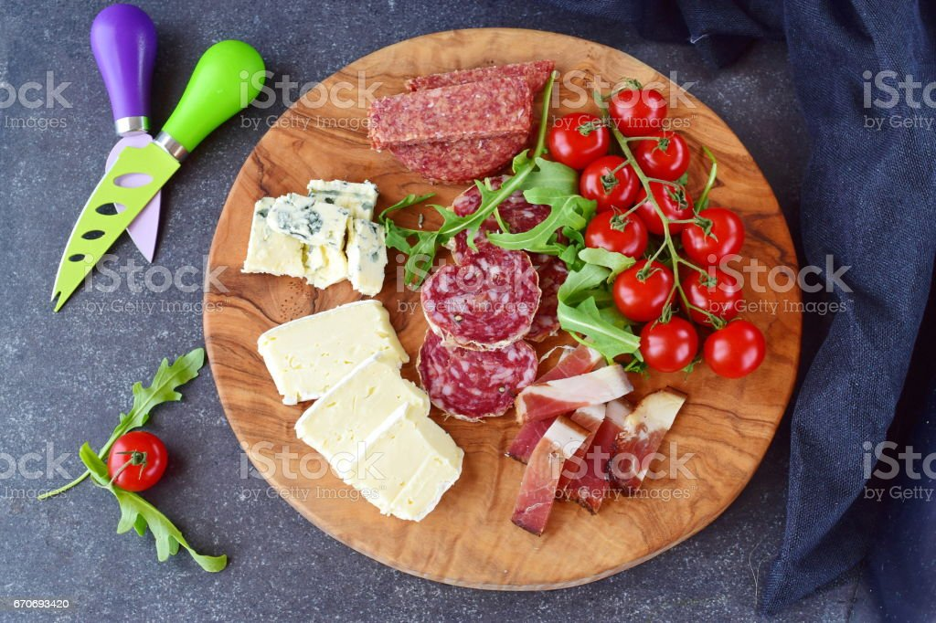Olive wood cutting board with cherry tomatoes, arugula and variety of sliced cheeses and sausages. Snack concept. stock photo