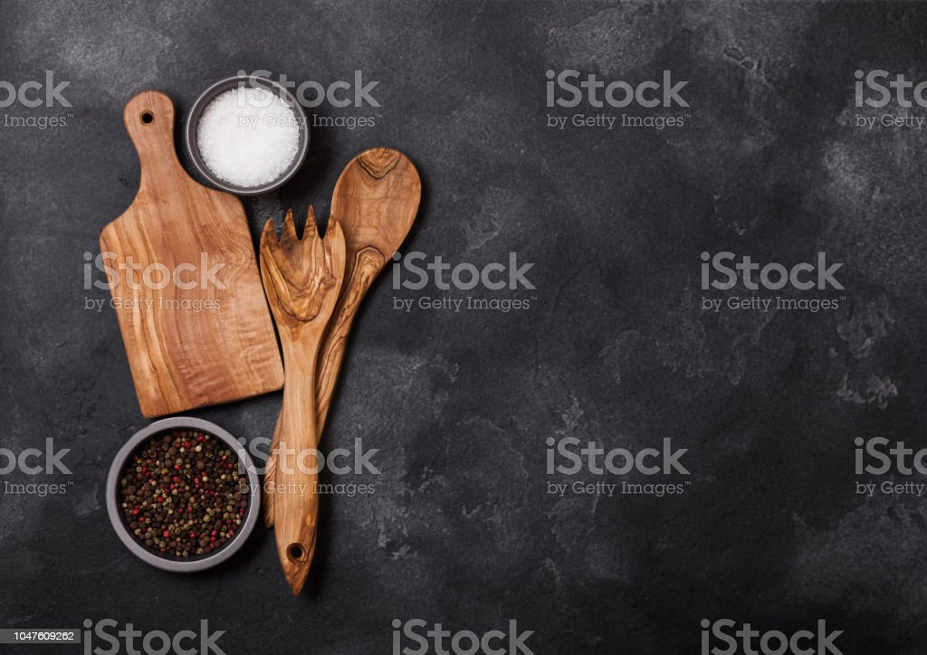 Olive wood kitchen utensils with chopping board on stone table...