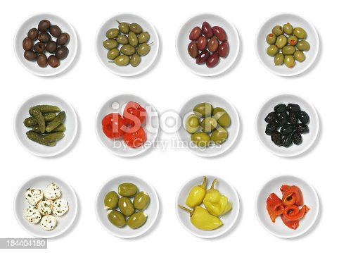 An assortment of olives and antipasto isolated on white.  From left to right, top to bottom, they are: pitted black olives, Greek olives, Kalamata olives, cocktail olives with pimentos, cornichons, sweet pickled red peppers, large green olives, dried olives, marinated mozzarella, feta stuffed olives, pepperoncinis, and roasted red peppers (pimentos).