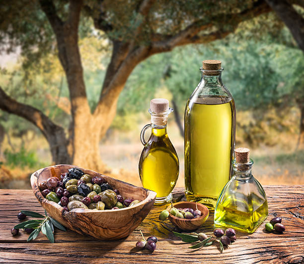 olives and olive oil on the nature background. - olive oil stock photos and pictures