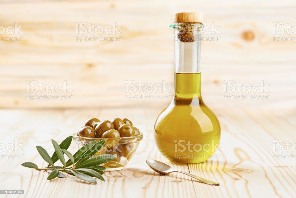 Aceitunas en recipiente de vidrio y aceite de oliva extra virgen - foto de stock