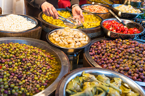 Olives in Sicily Open market in Catania,colorful olives, artichoke, stuffed chilli and other pickled dishes, and human hands taking food into small plastic. Sicily, Italy. catania stock pictures, royalty-free photos & images