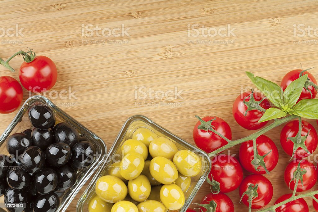 Olives, tomatoes and basil on cutting board royalty-free stock photo