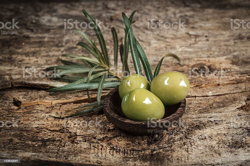 Olives with leaves on a wooden surface. stock photo