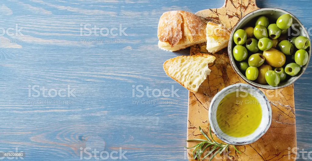Olivier oil with fresh herbs and bread. Blue background. Italian and Greek national food. Top view royalty-free stock photo
