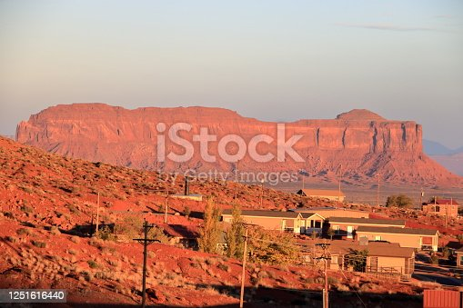 The light of the morning sun glows on the red rocks of the mesa