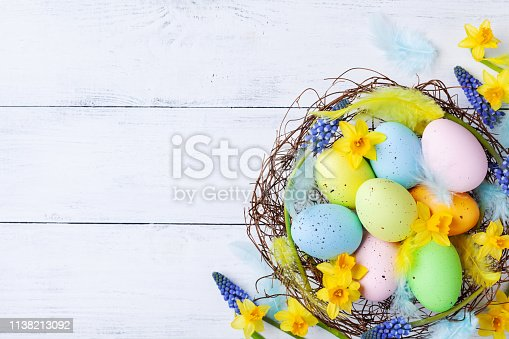 istock Сolorful Easter eggs in nest, feather and spring flowers on white table top view. Holiday card or banner. 1138213092