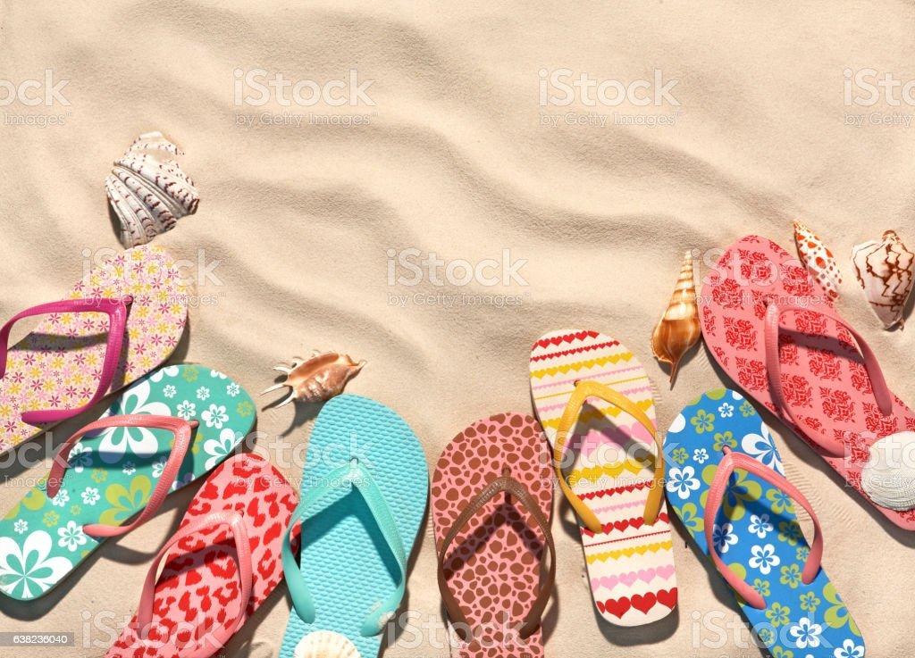 Сolorful flip flops on the sandy beach. stock photo