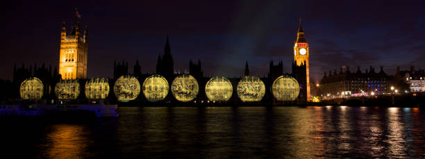 """Olympic Gold medals from 1948 projected onto Houses of Parliament """"London, United Kingdom - August, 11th 2012: View from Albert Embankment at night, looking across the River Thames, of Gold medals from the 1948 London Olympic Games being projected onto The Houses of Parliament. The projections depicting great moments from Olympic history were beamed each night for the duration of The London 2012 Olympic Games."""" 2012 stock pictures, royalty-free photos & images"""
