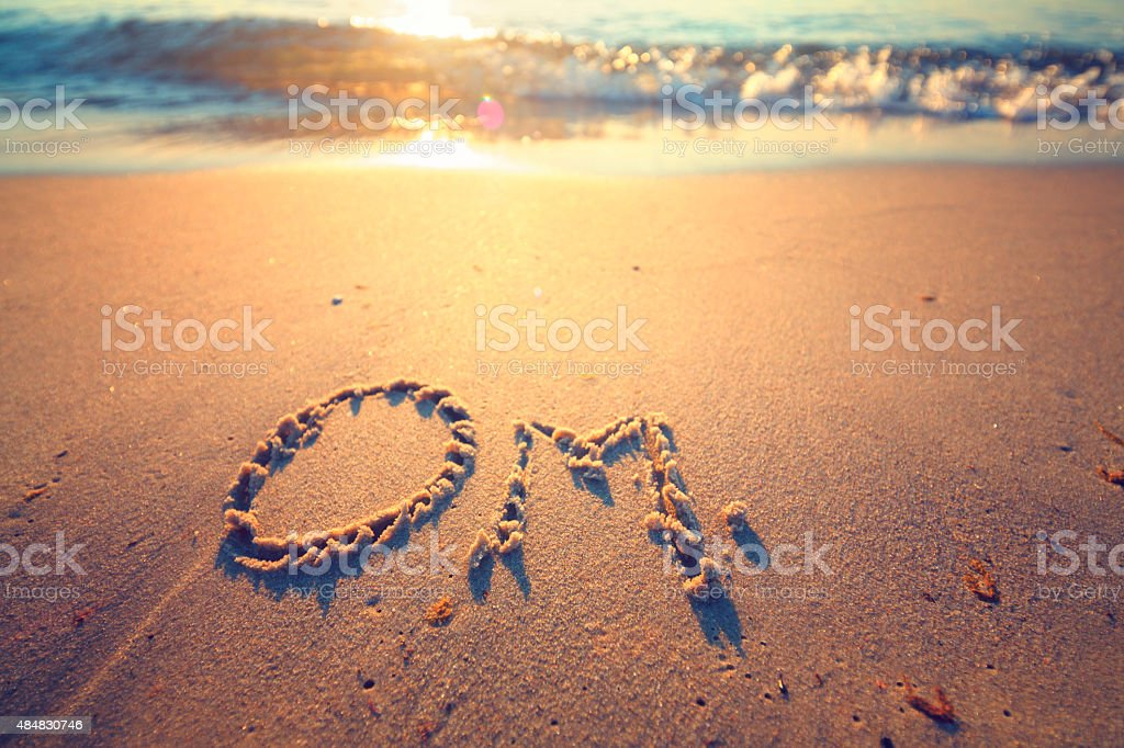 Om letter in the sand by the ocean stock photo