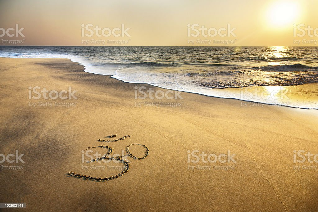 Om symbol on the beach stock photo