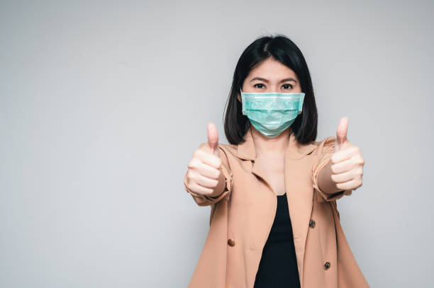 oman wearing face mask protect from virus showing thumb up stock photo