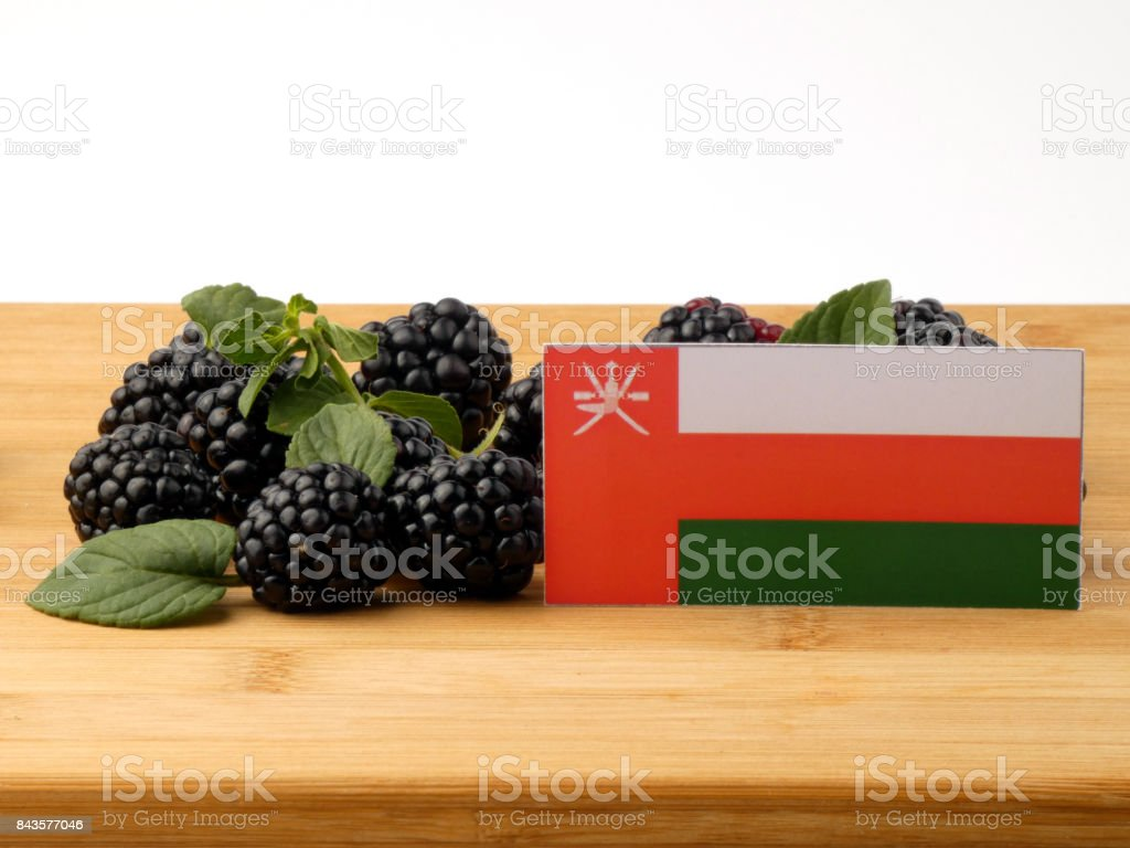 Omani flag on a wooden panel with blackberries isolated on a white background stock photo