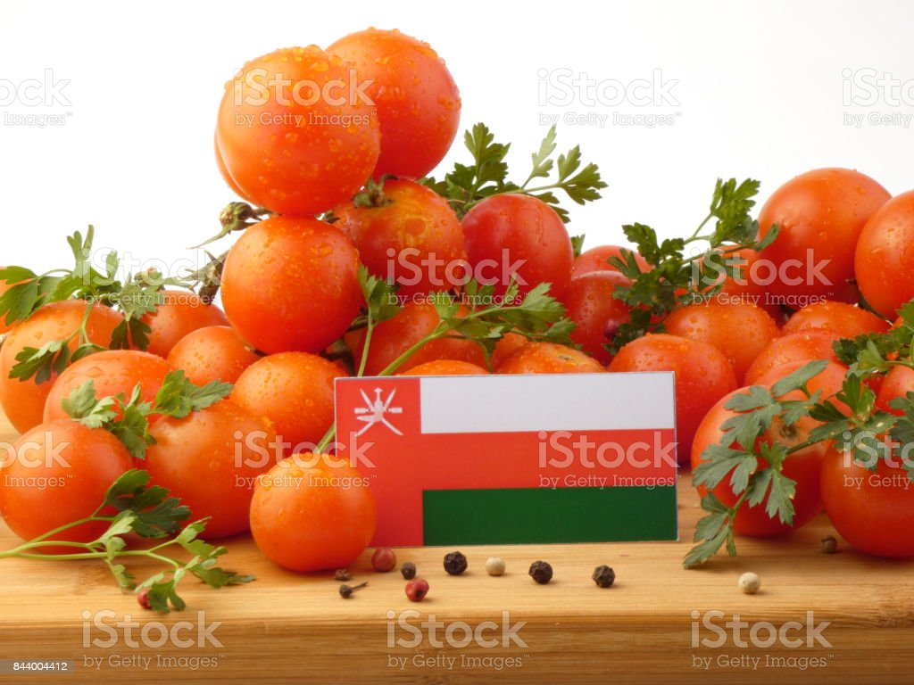 Omani flag on a wooden panel with tomatoes isolated on a white background stock photo