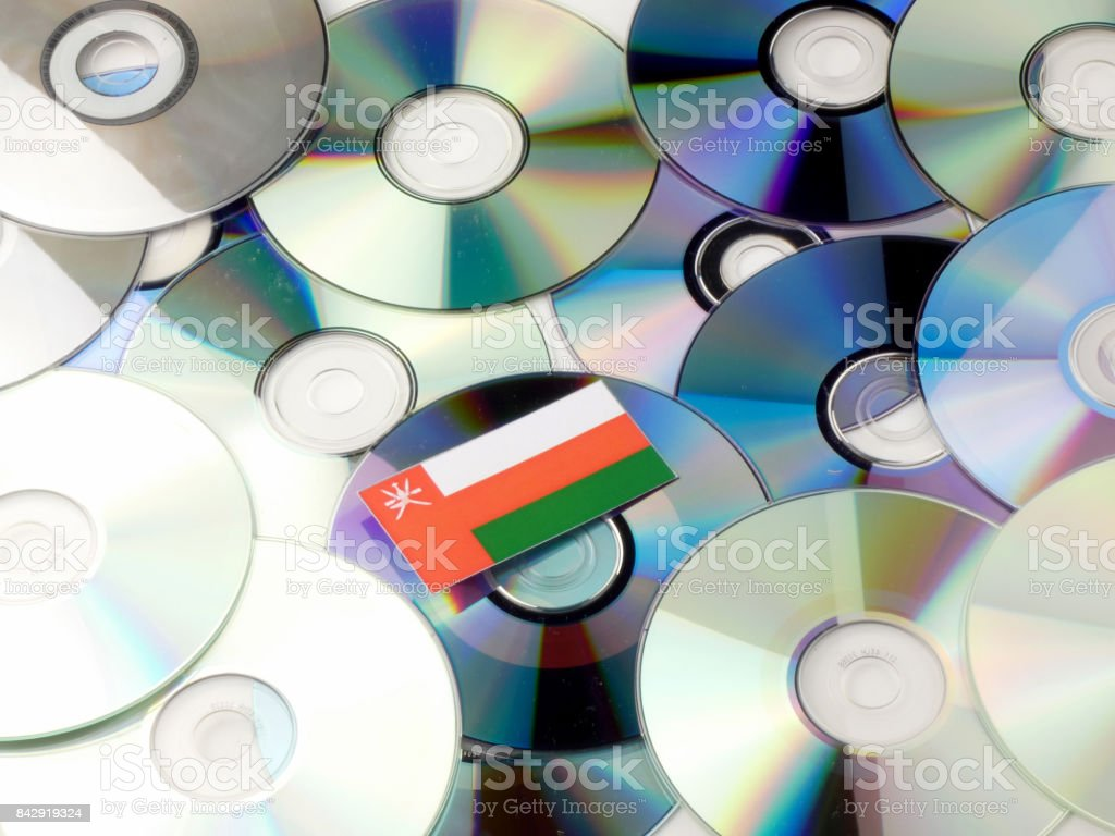 Omani flag on top of CD and DVD pile isolated on white stock photo