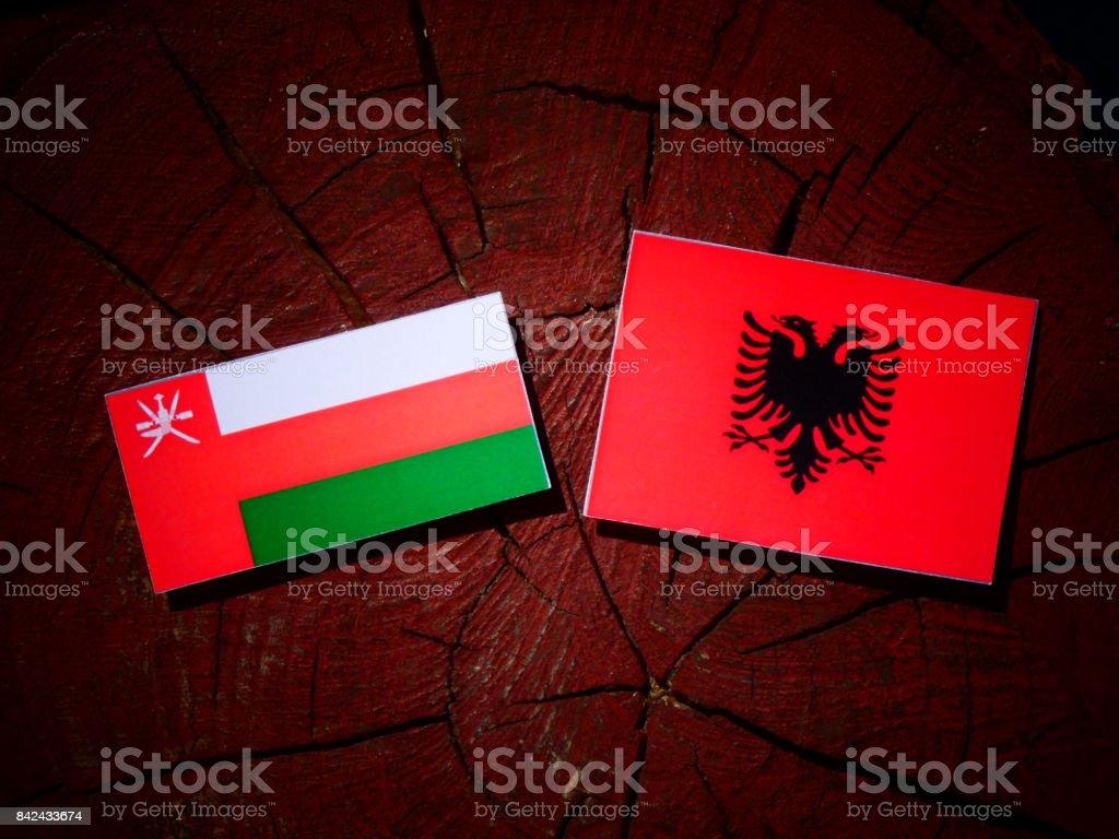 Omani flag with Albanian flag on a tree stump isolated stock photo