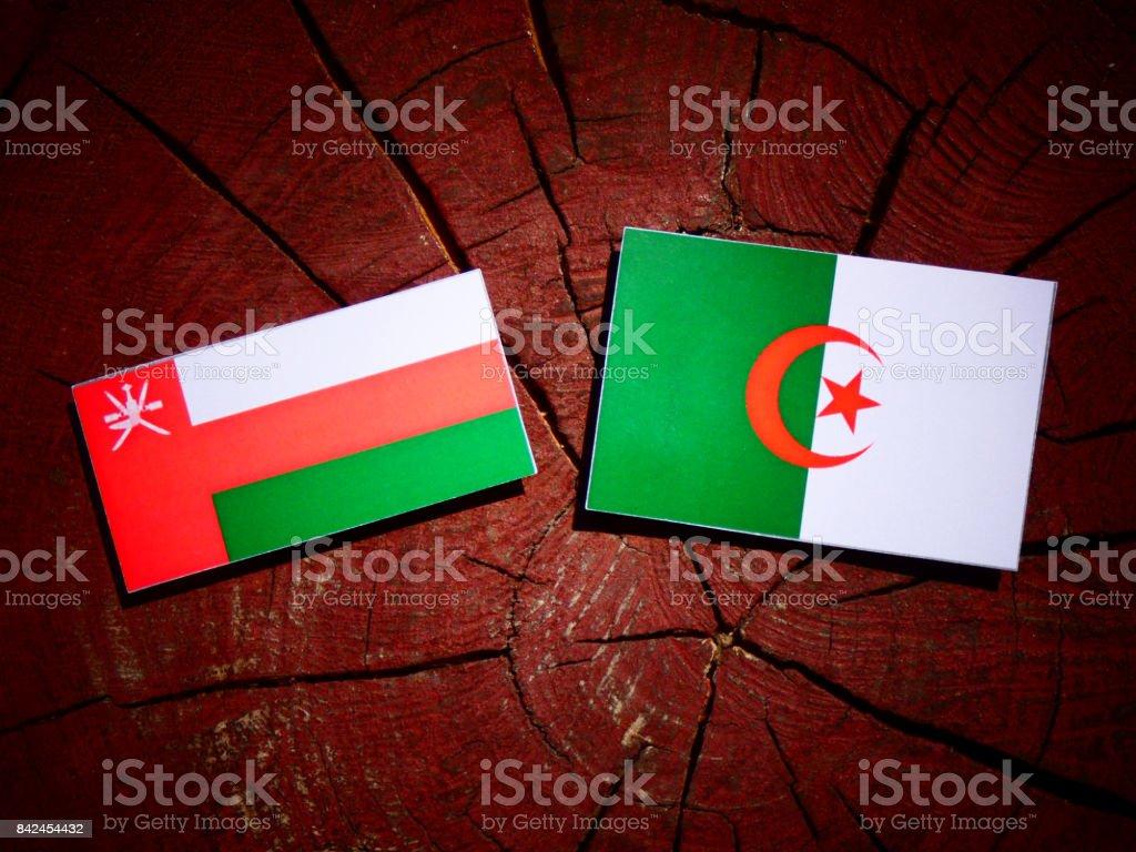 Omani flag with Algerian flag on a tree stump isolated stock photo
