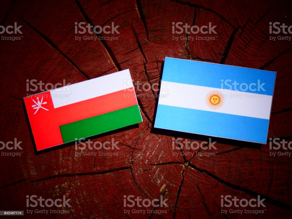 Omani flag with Argentinian flag on a tree stump isolated stock photo