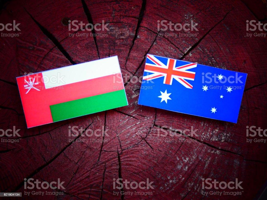 Omani flag with Australian flag on a tree stump isolated stock photo