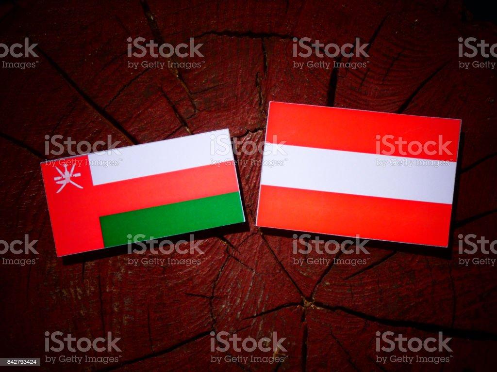 Omani flag with Austrian flag on a tree stump isolated stock photo