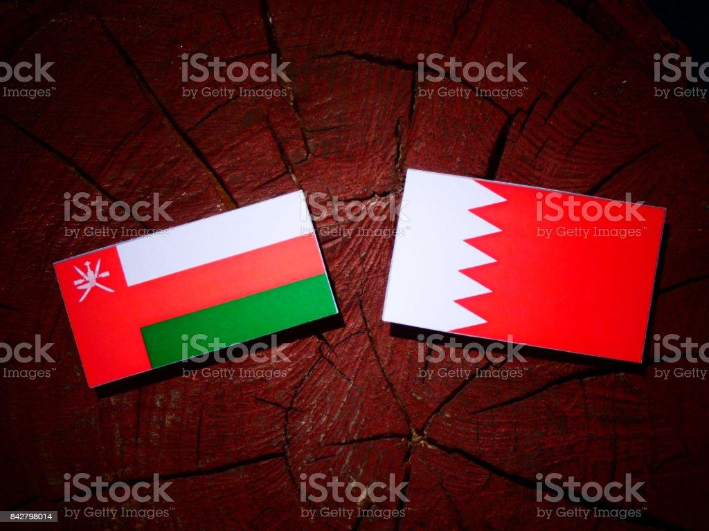 Omani flag with Bahraini flag on a tree stump isolated stock photo
