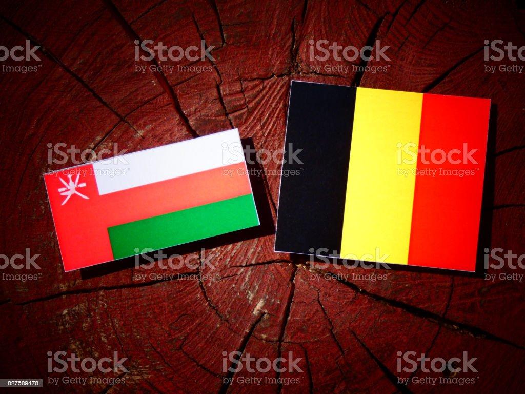 Omani flag with Belgian flag on a tree stump isolated stock photo