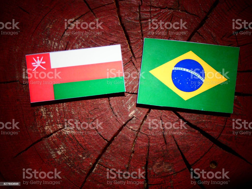 Omani flag with Brazilian flag on a tree stump isolated stock photo