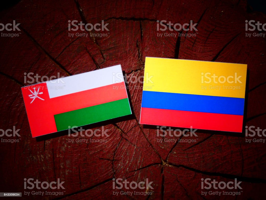 Omani flag with Colombian flag on a tree stump isolated stock photo