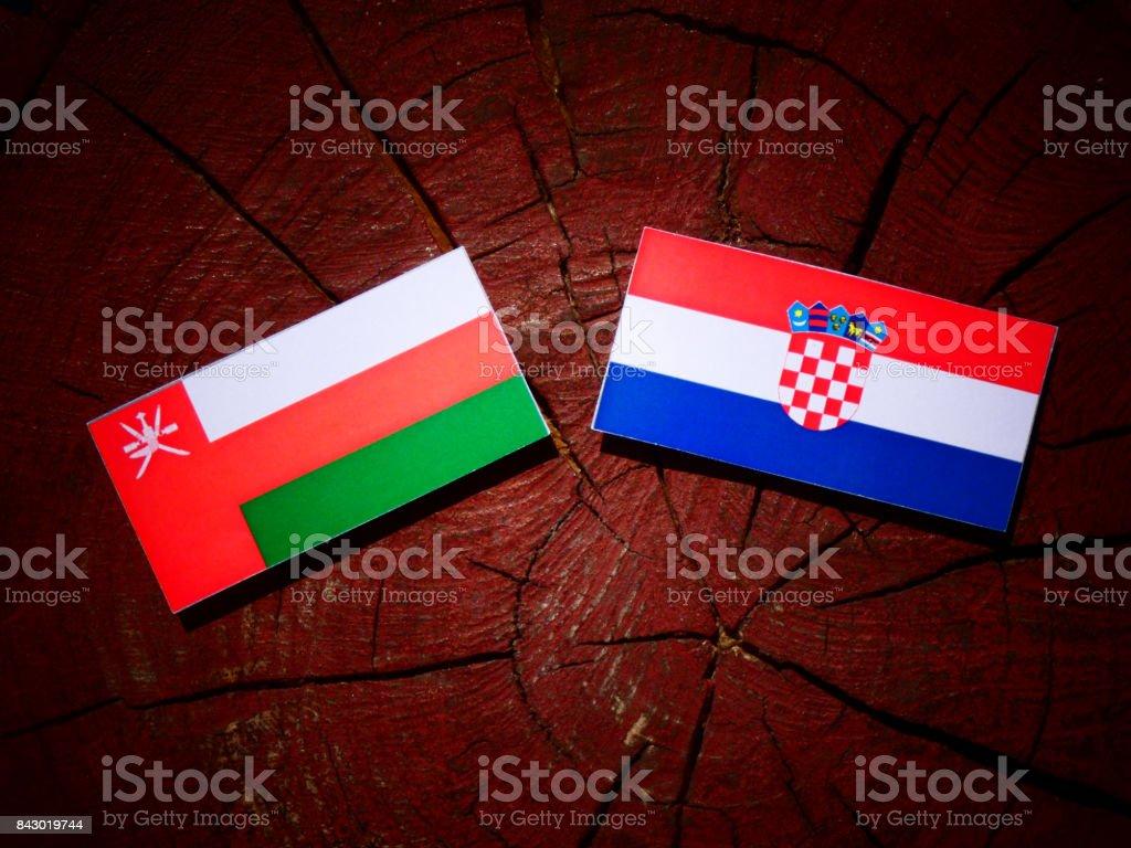 Omani flag with Croatian flag on a tree stump isolated stock photo