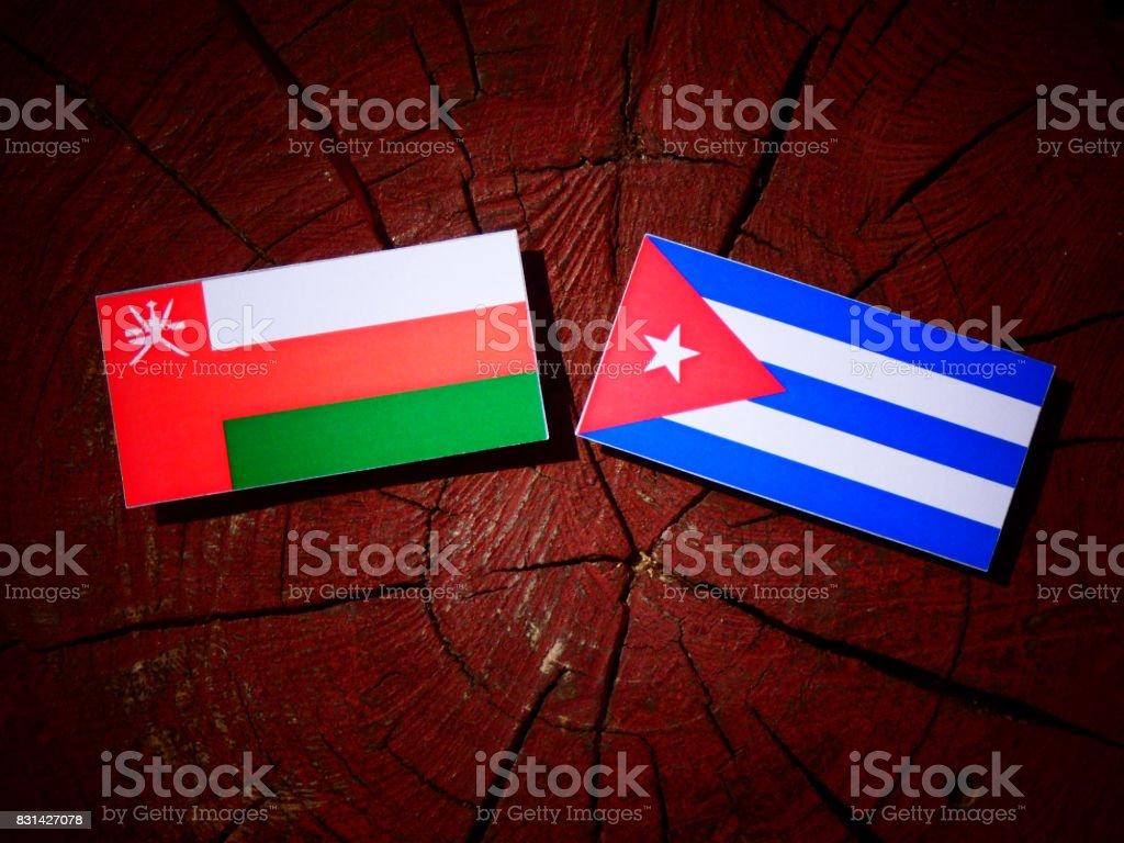 Omani flag with Cuban flag on a tree stump isolated stock photo