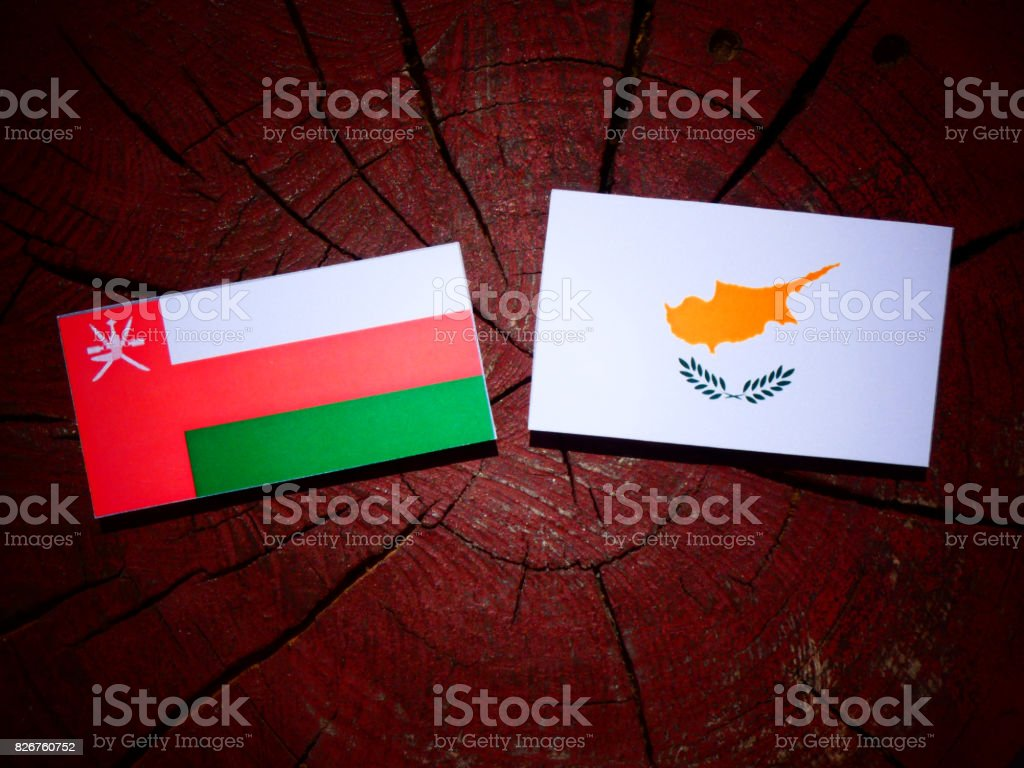 Omani flag with Cypriot flag on a tree stump isolated stock photo