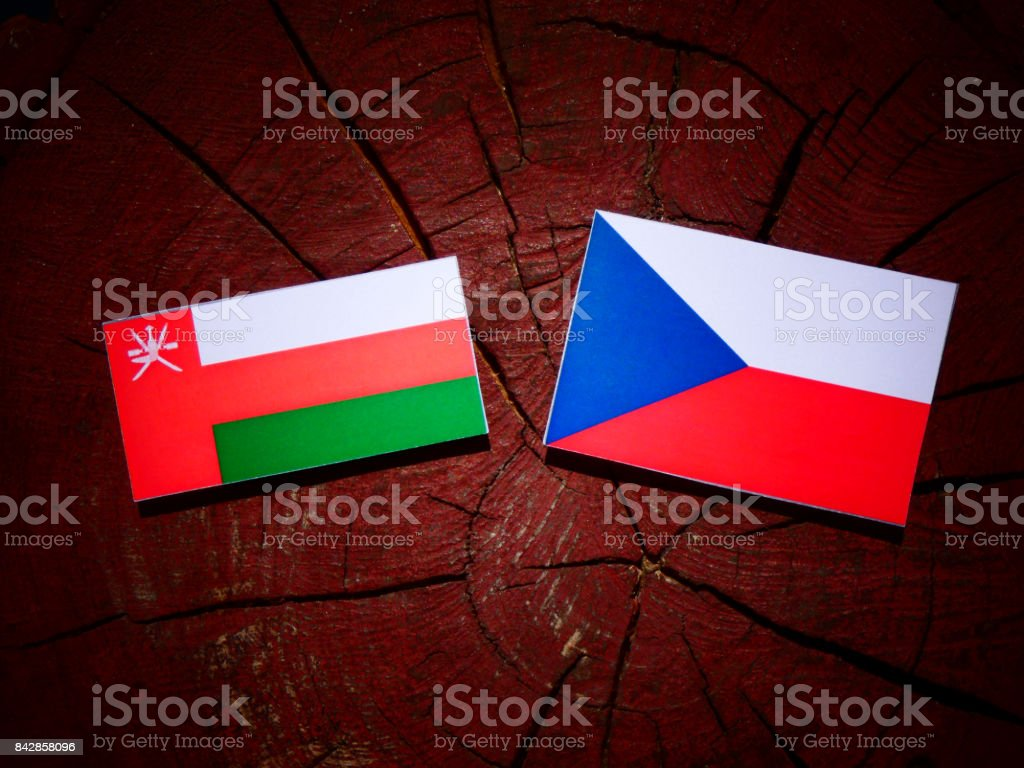 Omani flag with Czech flag on a tree stump isolated stock photo