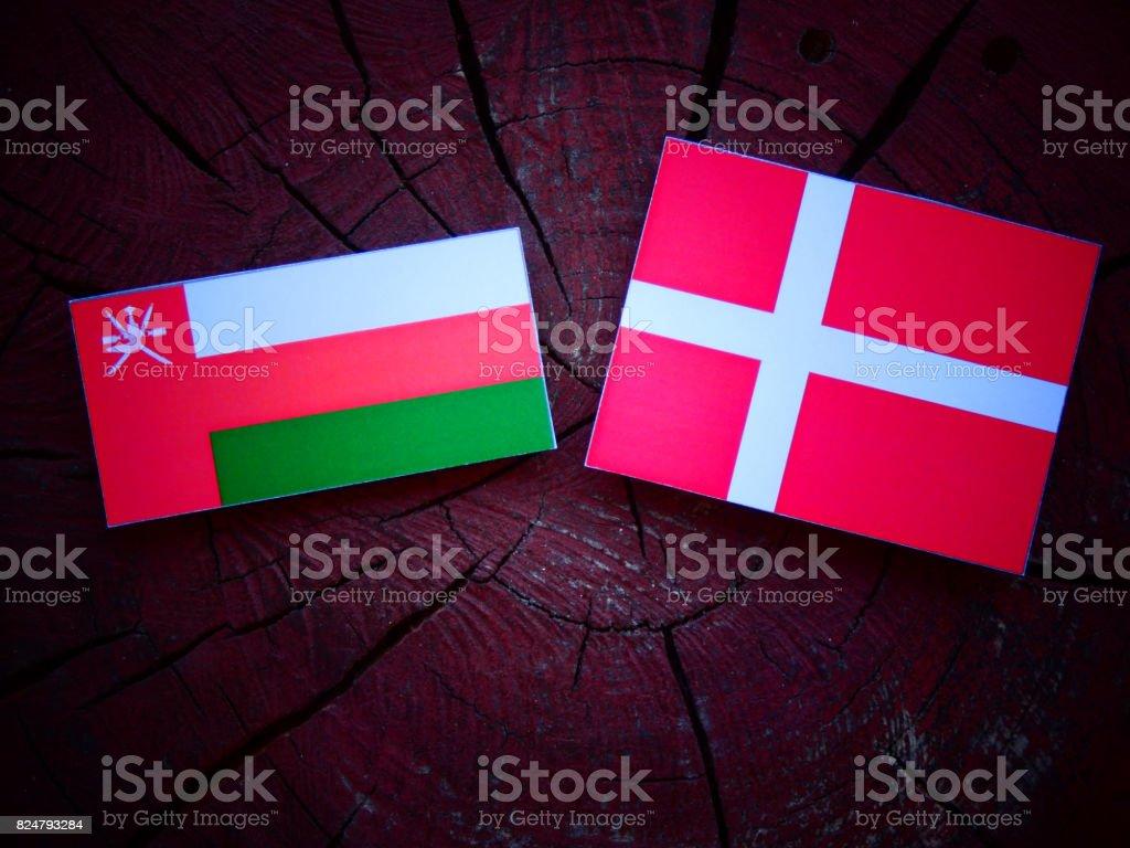 Omani flag with Danish flag on a tree stump isolated stock photo