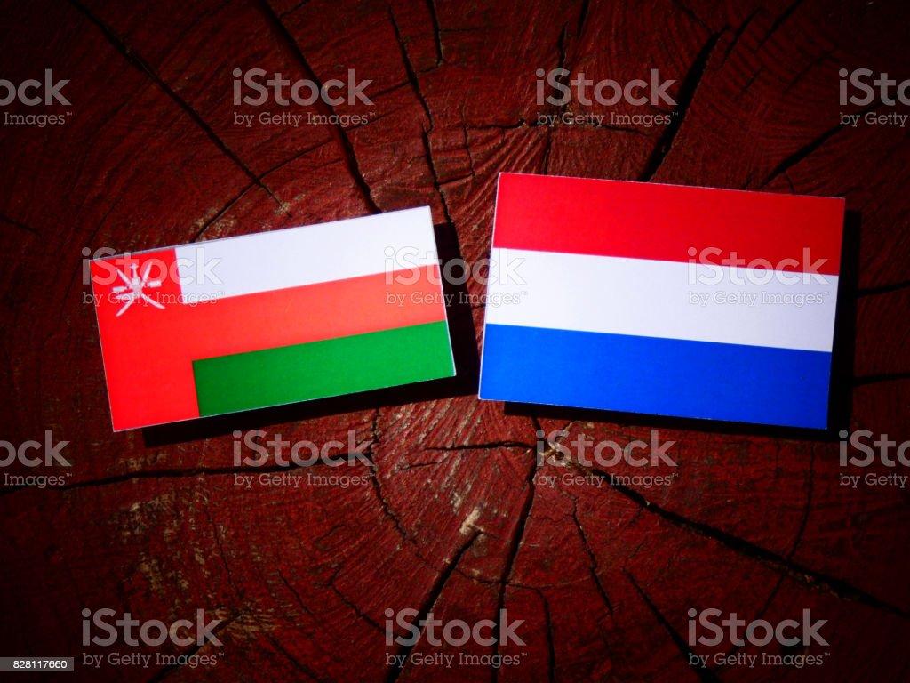 Omani flag with Dutch flag on a tree stump isolated stock photo