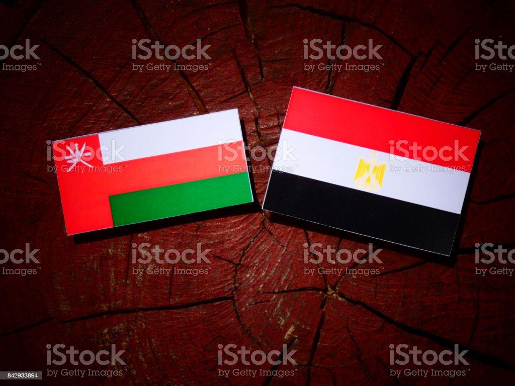 Omani flag with Egyptian flag on a tree stump isolated stock photo