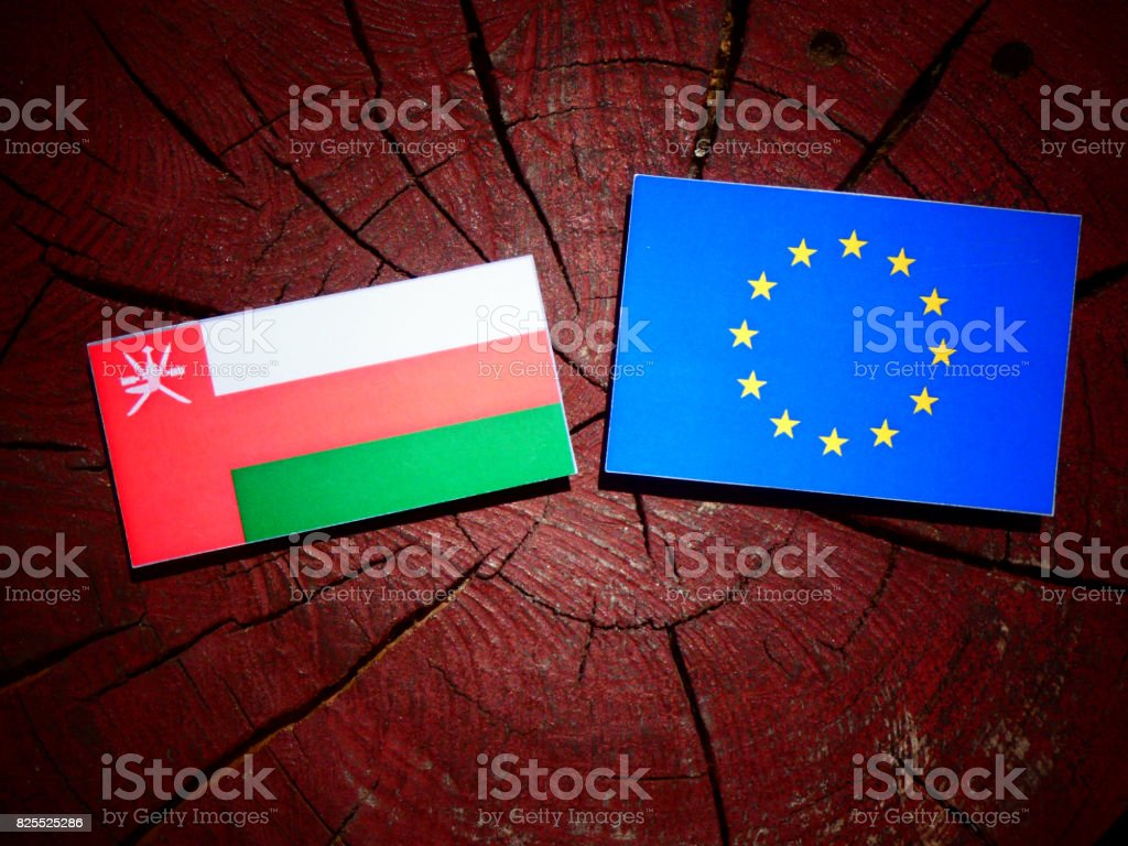 Omani flag with EU flag on a tree stump isolated stock photo