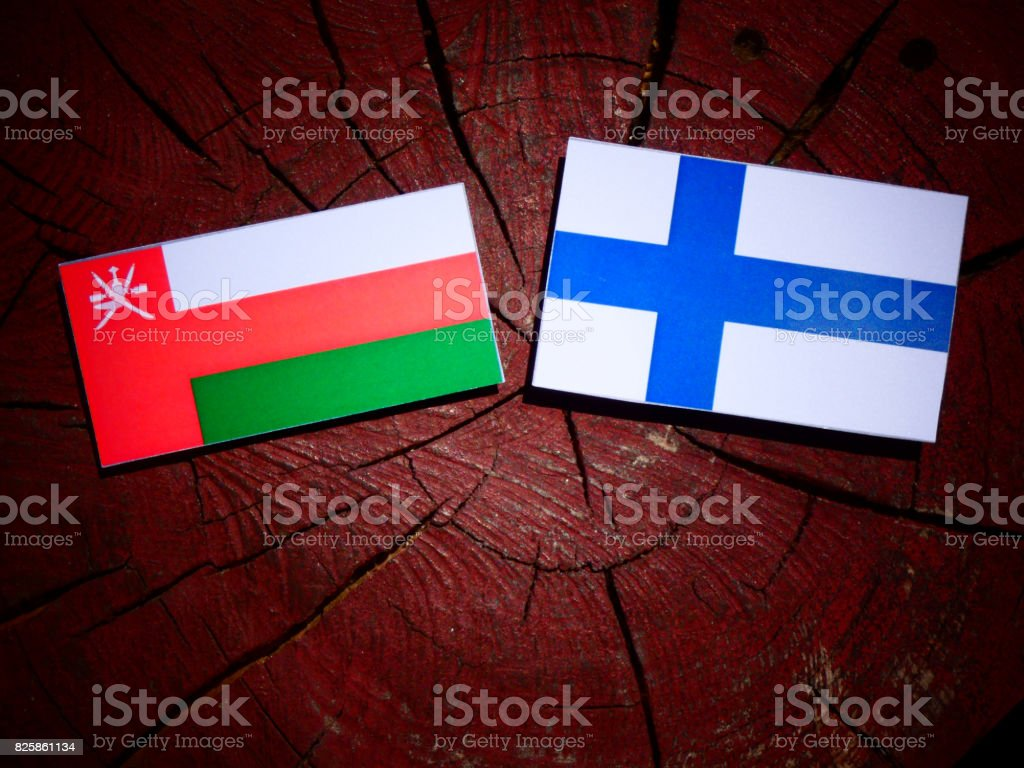 Omani flag with Finnish flag on a tree stump isolated stock photo