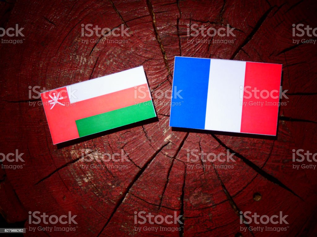 Omani flag with French flag on a tree stump isolated stock photo
