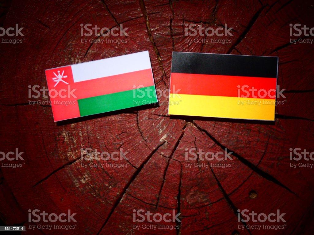 Omani flag with German flag on a tree stump isolated stock photo