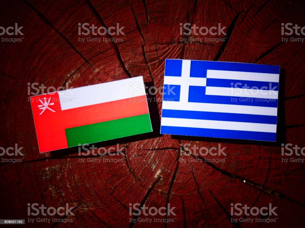 Omani flag with Greek flag on a tree stump isolated stock photo
