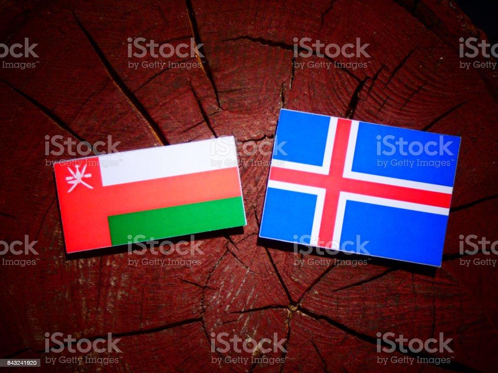 Omani flag with Icelandic flag on a tree stump isolated stock photo
