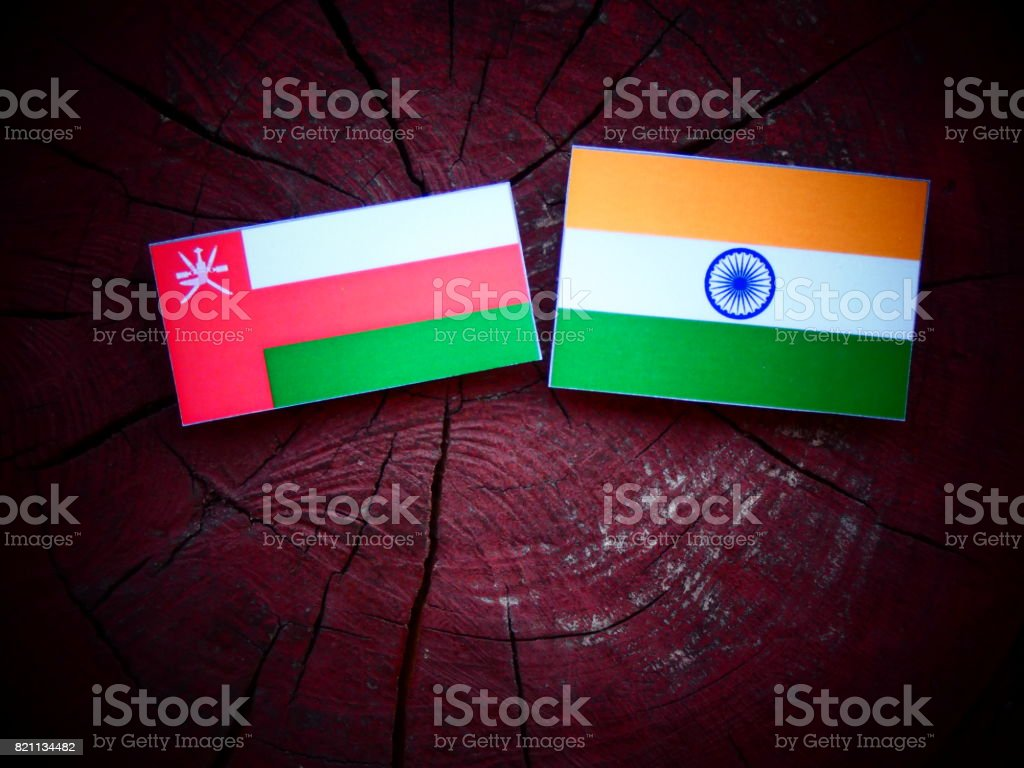 Omani flag with Indian flag on a tree stump isolated stock photo