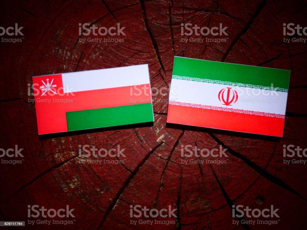 Omani flag with Iranian flag on a tree stump isolated stock photo
