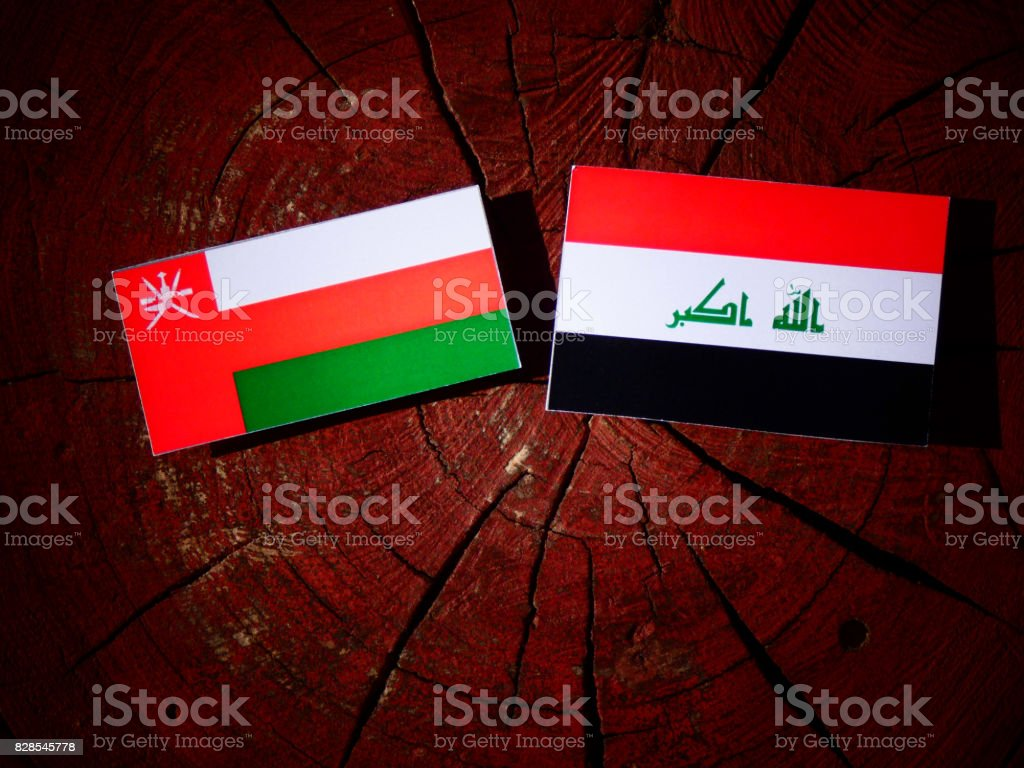 Omani flag with Iraqi flag on a tree stump isolated stock photo