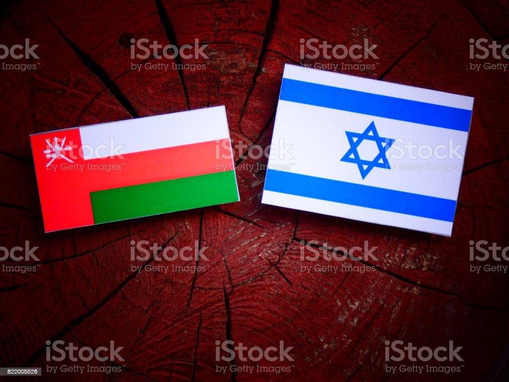 Omani flag with Israeli flag on a tree stump isolated stock photo