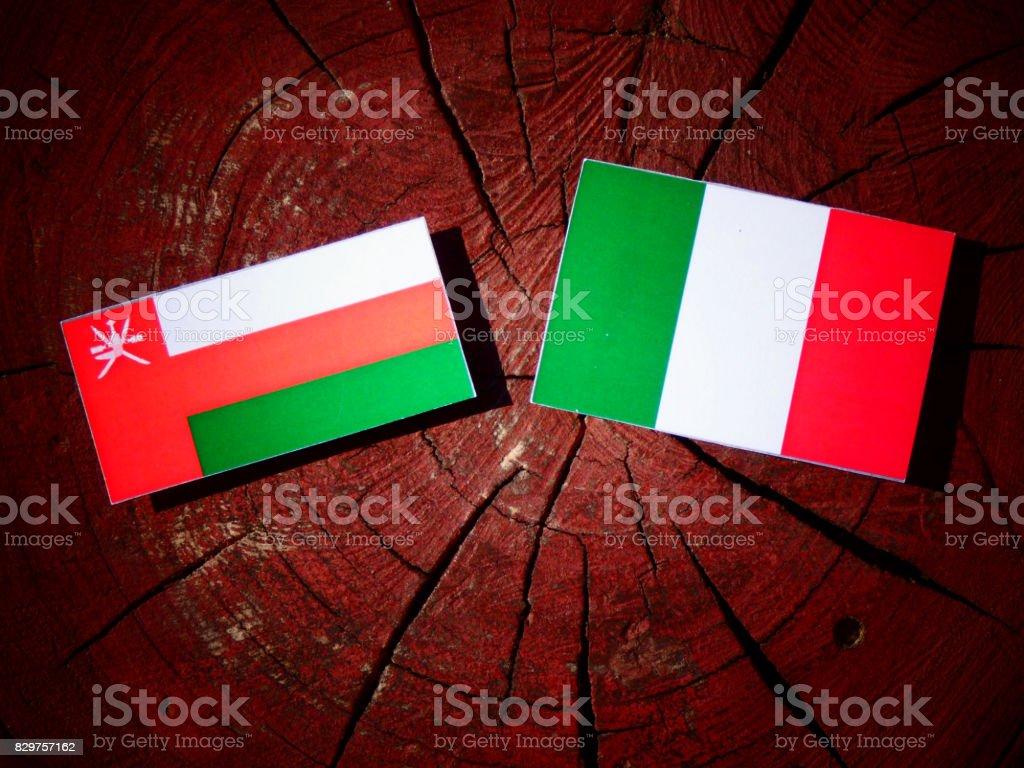 Omani flag with Italian flag on a tree stump isolated stock photo