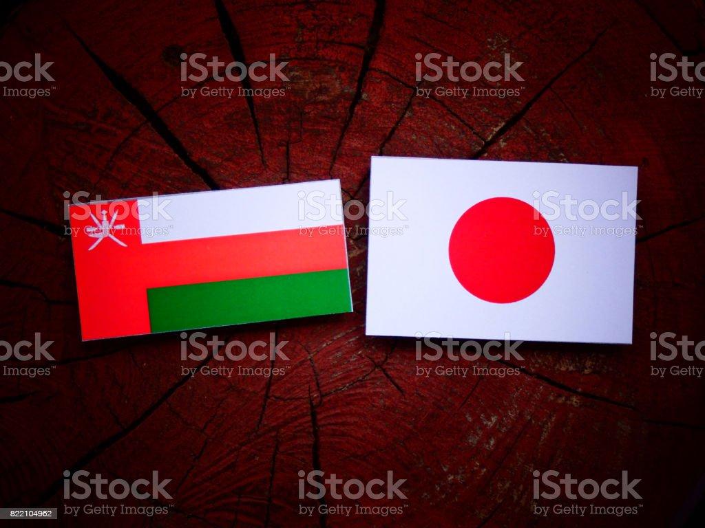 Omani flag with Japanese flag on a tree stump isolated stock photo