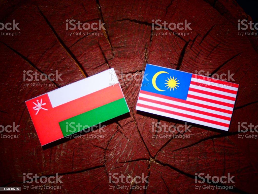 Omani flag with Malaysian flag on a tree stump isolated stock photo