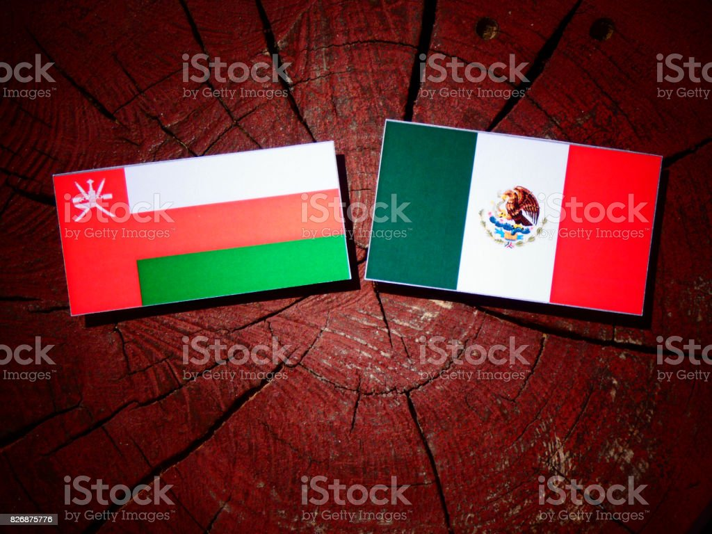 Omani flag with Mexican flag on a tree stump isolated stock photo